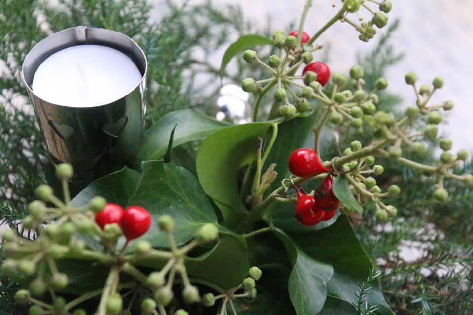 Kerststukje met kaarshouder en nep rode besjes.