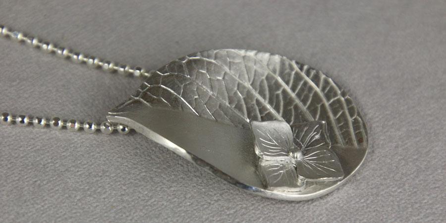 Zilveren Hortensia hanger aan een zilveren bolletjes collier.